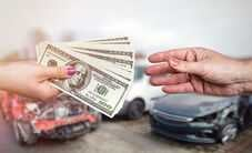 Money exchanging hands in front of crashed cars