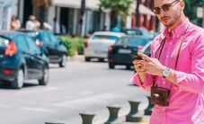 Man in pink shirt waiting for driver